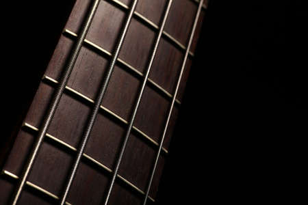 fretboard: Detail of the fret board of a bass guitar, on a dark background. Stock Photo