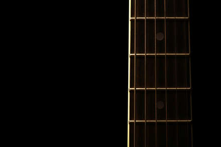 fret: Detail of the fret board of an acoustic guitar, on a dark background. Stock Photo