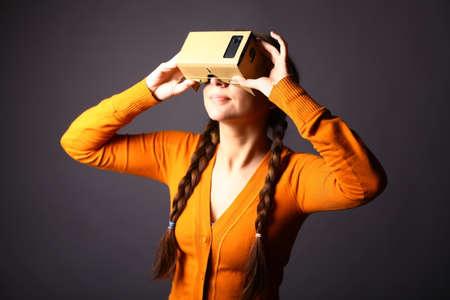 carton: Disparo de color de una mujer joven que busca a trav�s de un cart�n, un dispositivo con el que uno puede experimentar la realidad virtual en un tel�fono m�vil.