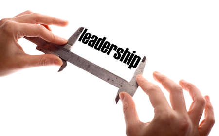 exact: Color horizontal shot of two hands holding a caliper and measuring the word leadership. Stock Photo