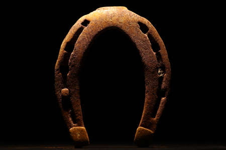 horse shoe: Color shot of a rusty horse shoe on a dark background.