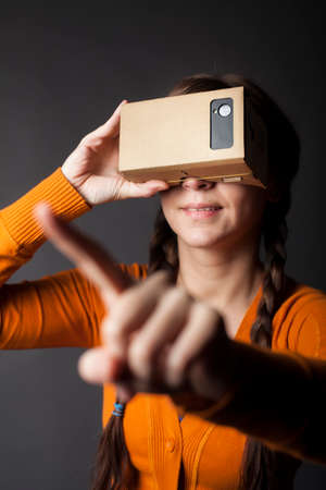 which one: Color shot of a young woman looking through a cardboard, a device with which one can experience virtual reality on a mobile phone. Editorial