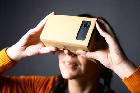 Color shot of a young woman looking through a cardboard, a device with which one can experience virtual reality on a mobile phone. Editorial
