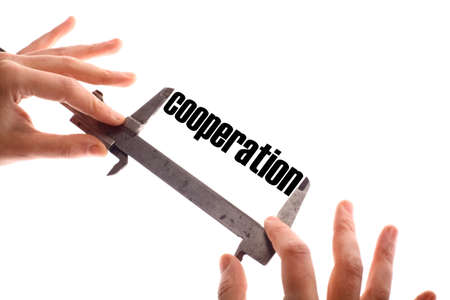 cooperate: Color horizontal shot of two hands holding a caliper and measuring the word cooperation. Stock Photo