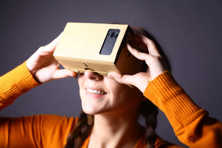 cardboards: Color shot of a young woman looking through a cardboard, a device with which one can experience virtual reality on a mobile phone. Stock Photo