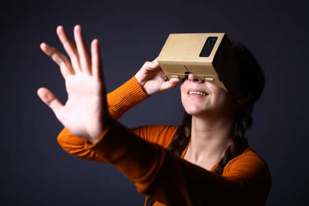 Color shot of a young woman looking through a cardboard, a device with which one can experience virtual reality on a mobile phone. Stock Photo