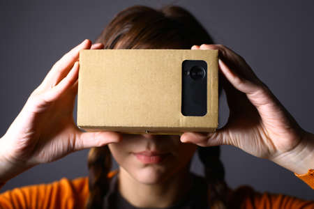 Color shot of a young woman looking through a cardboard, a device with which one can experience virtual reality on a mobile phone. 免版税图像