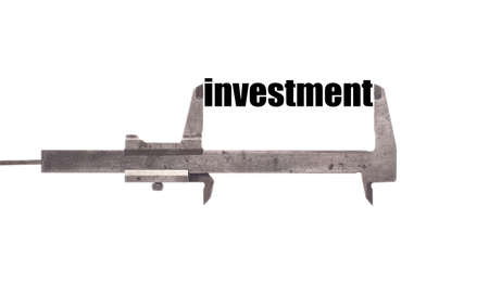 exact: Color horizontal shot of a caliper measuring the word investment. Stock Photo