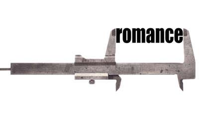 caliper: Color horizontal shot of a caliper measuring the word romance. Stock Photo