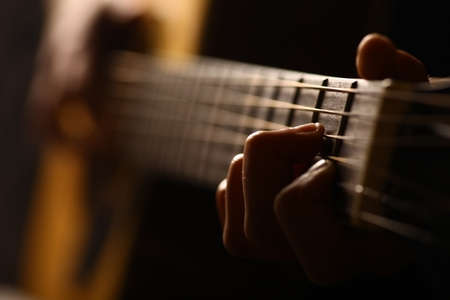 Color detail of hands playing of an old, acoustic guitar. Stockfoto