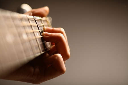 Color detail of hands playing of an old, acoustic guitar. Stock Photo