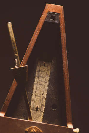allegro: Vertical shot of a vintage metronome, on a black background.