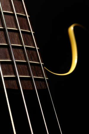 fret: Horizontal detail of the fret board of a bass guitar, on a dark background. Stock Photo
