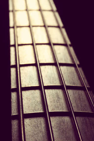 fret: Detail of the fret board of a bass guitar, on a dark background. Stock Photo