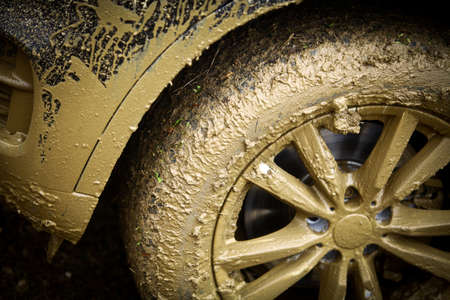 Color detail shot of an off-road cars wheel, covered in mud.