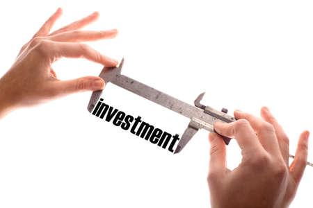 business symbols metaphors: Color horizontal shot of two hands holding a caliper and measuring the word investment. Stock Photo