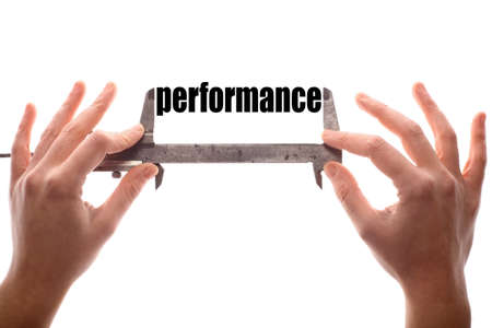 perform performance: Color horizontal shot of two hands holding a caliper and measuring the word performance.