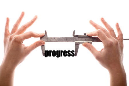 caliper: Color horizontal shot of a caliper measuring the word progress. Stock Photo