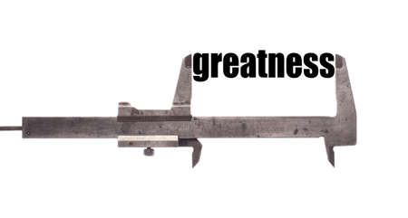 greatness: Color horizontal shot of a caliper, measuring the word greatness. Stock Photo