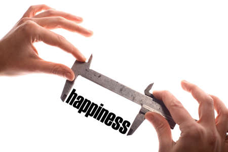 jubilation: Color horizontal shot of two hands holding a caliper and measuring the word happiness.