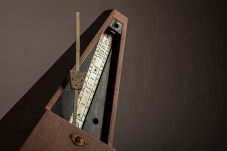 wood tick: Color shot of a vintage metronome, on a black background.
