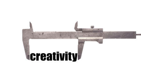 caliper: Color horizontal shot of a caliper measuring the word creativity.