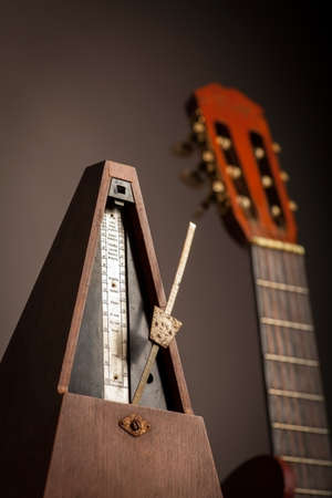 Color shot of a vintage metronome, next to an acoustic guitar, on a black background. photo