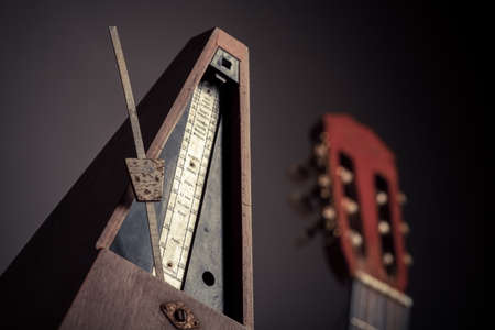allegro: Color shot of a vintage metronome, next to an acoustic guitar, on a black background.