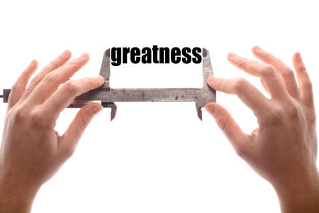 greatness: Color horizontal shot of two hands holding a caliper, measuring the word greatness.