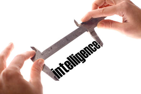 exact: Color horizontal shot of two hands holding a caliper measuring the word intelligence.
