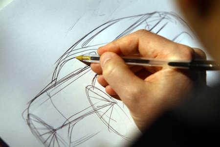 Close-up shot van de hand van een persoon het schetsen van een concept car.