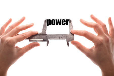 dominance: Color horizontal shot of two hands holding a caliper measuring the word power.