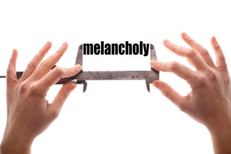 melancholy: Color horizontal shot of two hands holding a caliper measuring the word melancholy.