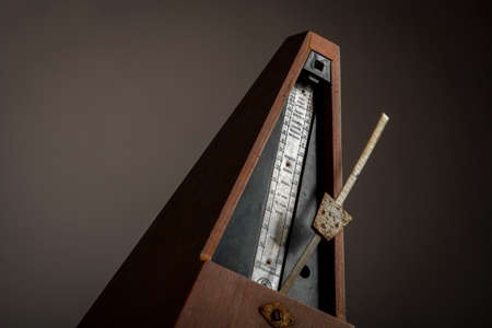 allegro: Color shot of a vintage metronome, on a black background.