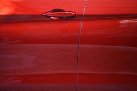 Color detail of a red car door handle. Stock Photo