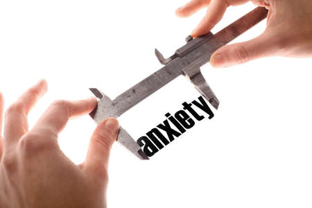 anxiety: Color horizontal shot of two hands holding a caliper measuring the word anxiety.