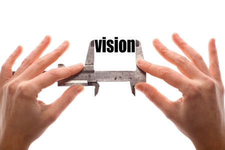 foresight: Color horizontal shot of two hands holding a caliper and measuring the word vision.