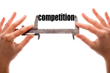 competitiveness: Color horizontal shot of two hands holding a caliper and measuring the word competition.