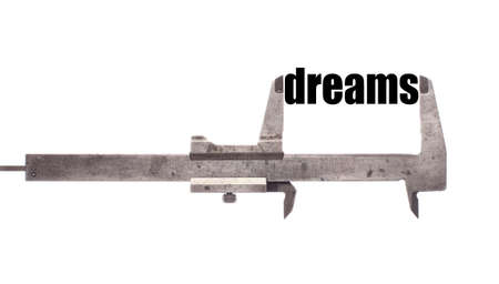 caliper: Color horizontal shot of a caliper and measuring the word dreams. Stock Photo