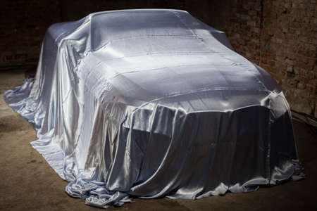 concealed: Color shot of a car under a white cover. Stock Photo