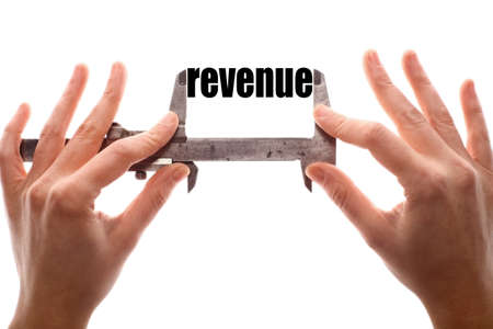 Color horizontal shot of two hands holding a caliper and measuring the word revenue.