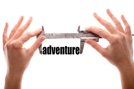 uncertainty: Color horizontal shot of two hands holding a caliper and measuring the word adventure. Stock Photo
