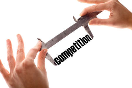 enemies: Color horizontal shot of two hands holding a caliper and measuring the word competition.