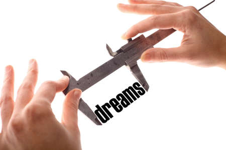 accomplish: Color horizontal shot of two hands holding a caliper and measuring the word dreams. Stock Photo