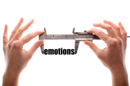 humanism: Color horizontal shot of two hands holding a caliper measuring the word emotions.
