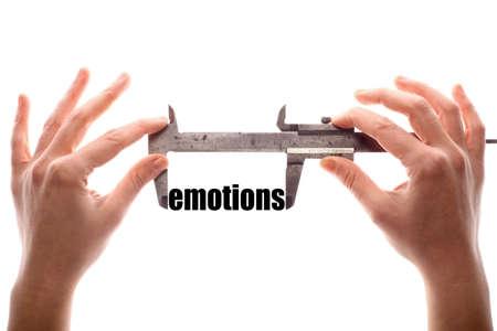 """humanismo: Tiro horizontal de color de dos manos que sostienen una pinza de medición de la palabra """"emociones""""."""
