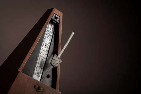 Color shot of a vintage metronome, on a black background. photo