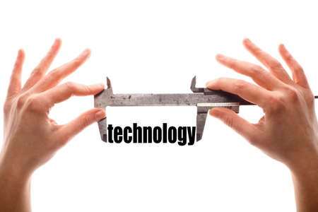 caliper: Color horizontal shot of two hands holding a caliper and measuring the word technology.
