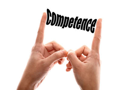 suitability: Color horizontal shot of two hands squeezing the word competence. Stock Photo