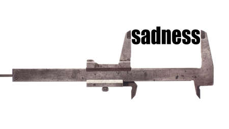 pain scale: Color horizontal shot of a caliper and measuring the word sadness.